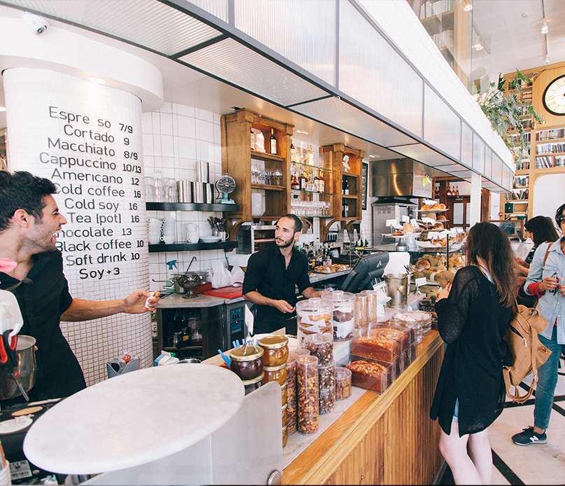 Coffee shop cashier and barista with customers