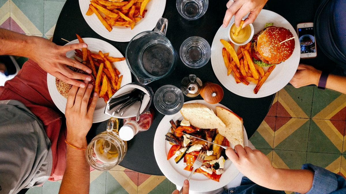 A group eating burgers and fries at a restaurant